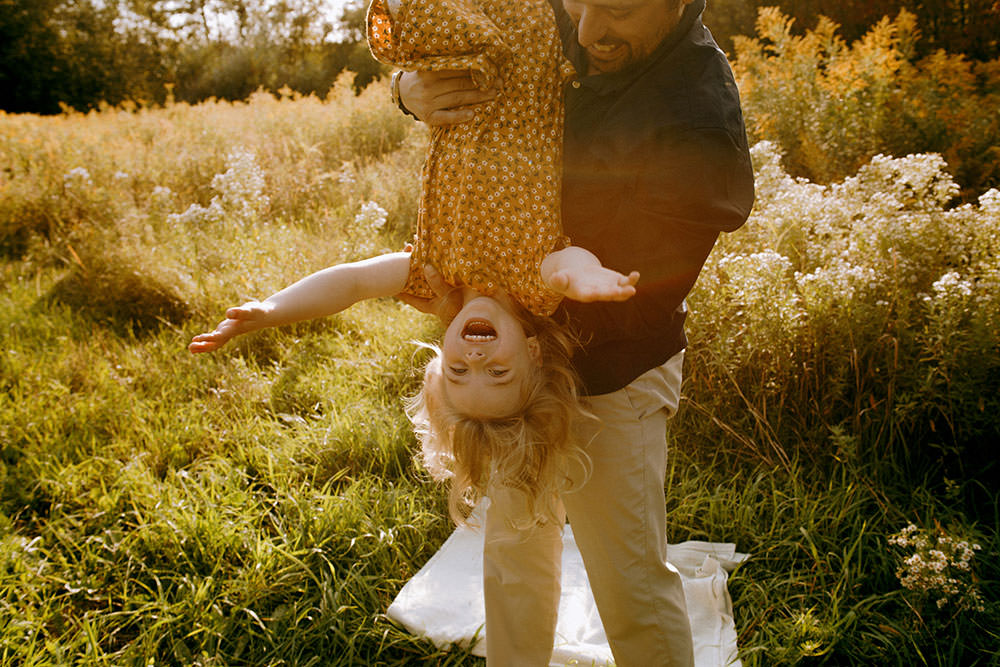 Sudbury family photography of dad swinging toddler upside down laughing