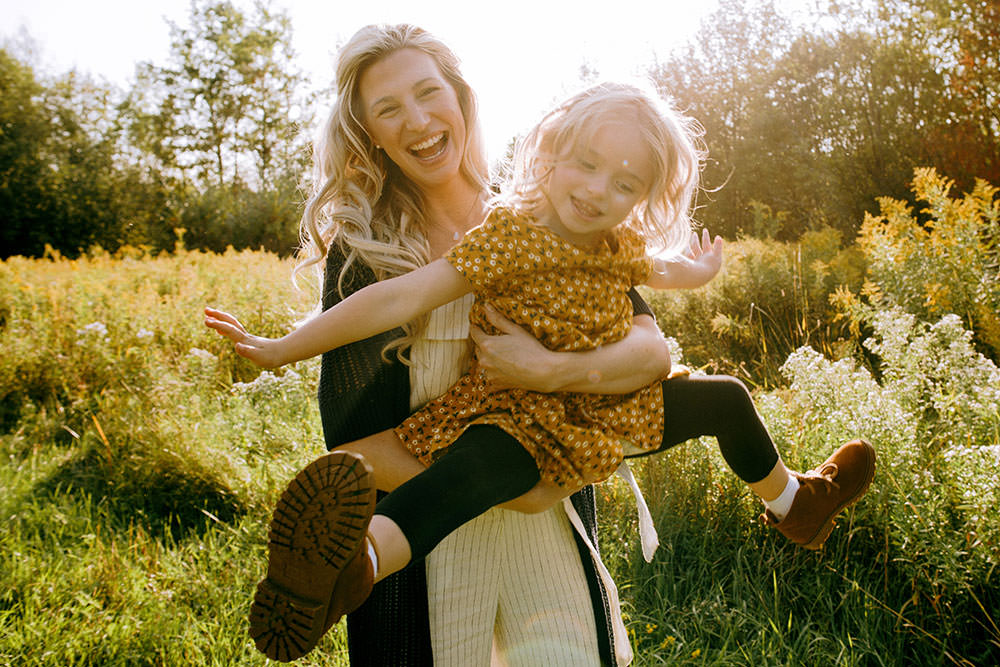 Sudbury family photography of mom lifting daughter laughing together