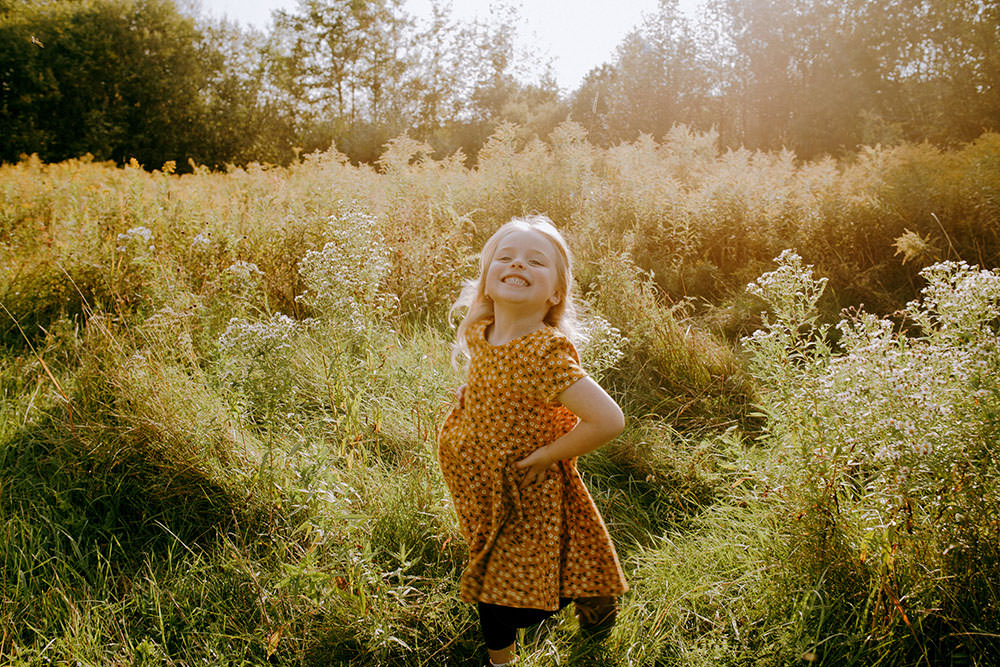 Sudbury family photography of daughter laughing in flower field