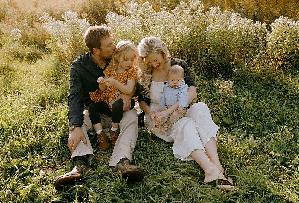 Sudbury family photography of family sitting together in flower field