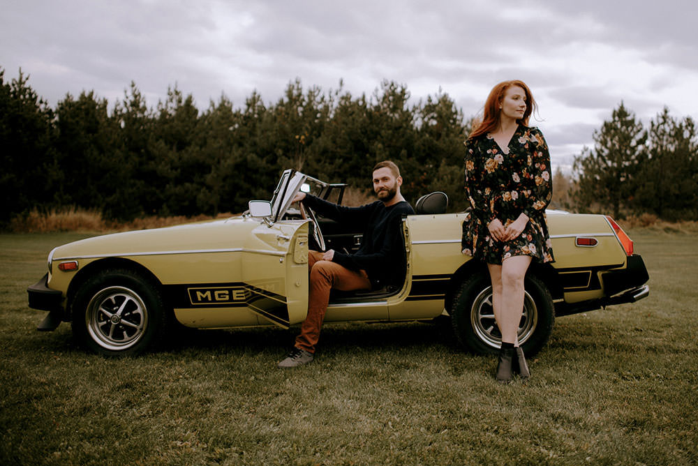 Fairbanks Ontario engagement photography of couple holding each other on MGB classic car